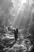 Woman and child walking in forest during first field trip with Margaret Mead to Bali, December 1957 - January 1958