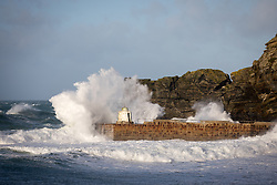 © Licensed to London News Pictures. 01/01/2018. Portreath, UK. Large waves crash into Portreath harbour wall and Portreath beach. The remainders of Storm Dylan have brought strong winds and heavy rainfall, and Storm Eleanor is due to arrive on Wednesday. Photo credit : Tom Nicholson/LNP