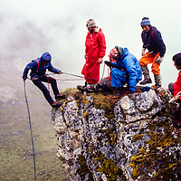 American guides teach clinbing sherpas how to rappel in the rain at an early mountaineering school for sherpas in the Khumbu region of Nepal, 1980.