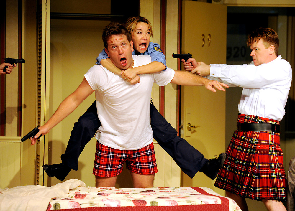 """Jennifer Cody playing Billie Dwyer jumps out of the closet on to Jeremy Webb playing Todd with John Scherer as Eric Sheridan pointing a gun in the background during a run-through of """"Unnecessary Farce"""" at the Cape Cod Playhouse."""