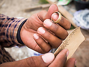 04 SEPTEMBER 2013 - BANGKOK, THAILAND:  A Cambodian construction worker buffs a piece of jewelry he is making after his shift. He lives in corrugated metal dorms on the construction site of a new high rise apartment / condominium building on Soi 22 Sukhumvit Rd in Bangkok. Most of the workers at the site are Cambodian immigrants.    PHOTO BY JACK KURTZ