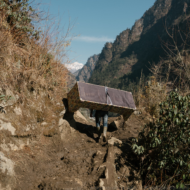 A man carrying a couch to his home. From the end of the dirt road, it takes 7 hours to trek up to Laya village.