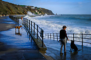 A man stands on the promenade looking out to sea with his two dogs near by on Sunny Sands Beach on 8th December 2018 in Folkestone, Kent, UK. The tide is high covering all the beach and the sea is rough from stormy weather.