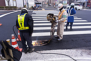 road repair workers burning the pedestrian white stripes of the asphalt Japan