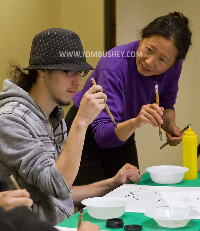 Middletown, N.Y. - Artist Gar Wang shows a student how to hold a brush during a calligraphy and painting Master Class given by her husband Ron Gee at SUNY Orange on Nov. 14, 2013.