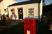 The shadows of two passing locals approach the tiny Cameron-run post office hut at Kyleakin on the Isle of Skye, Scotland. We see in the foreground the freshly painted Royal Mail post box which is lit by early morning sunshine telling us that the next collection is at 2.45pm despite it being 8.50am. This branch serves the local community of this Skye town, close to the Skye Bridge and is not only a place to post letters and packages but to buy miscellaneous supplies like newspapers and food at a time when rural sub-post offices are threatened with closure by a financially-troubled Royal Mail. Small villages like this often say that the post office is the ties its folk together, acting as a nucleus for information about village life. Their closure would therefore mean that the fabric of such remote communities are in jeopardy.