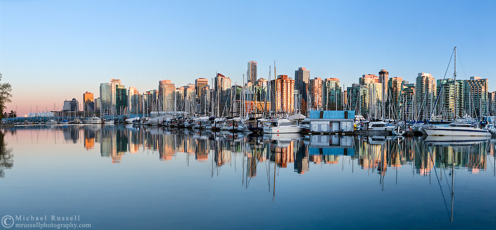 Sunset on the buildings of downtown Vancouver and the yachts and boats in the Royal Vancouver Yacht Club in Vancouver, British Columbia, Canada