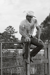 cowboy with a dirty tee shirt sitting on a fence