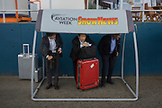 Trade delegates take cover under an aviation magazine shelter during rain at the Farnborough Air Show.