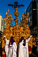 Hooded Penitents (Nazarenos) and a paso (float) of The Crucifixion of Jesus Christ in the procession of the Brotherhood (Hermandad) San Benito, Holy Week (Semana Santa), Seville, Andalusia, Spain.