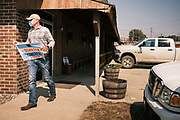 """22 SEPTEMBER 2020 - DUNLAP, IOWA: Congressional candidate J.D. SCHOLTEN leaves Dunlap Livestock Auction with one of his campaign yard signs. Scholten, a Democrat from Sioux City, Iowa, ran against incumbent CongressmanSteve King (R-4th District Iowa) in 2018 and came within a few percentage points of upsetting the long serving conservative. King lost to Randy Feenstra, a Republican challenger, in the 2020 primary and Scholten is running against Feenstra in the 2020 general election on November 3. Iowa's 4th district, centered in the agricultural and sparsely populated northwest corner of the state, is the largest congressional district in Iowa and encompasses about ⅓ of the state of Iowa. Scholten is on his """"Every Town Tour 2020."""" He is visiting all 375 towns in the 39 counties in the district.    PHOTO BY JACK KURTZ"""