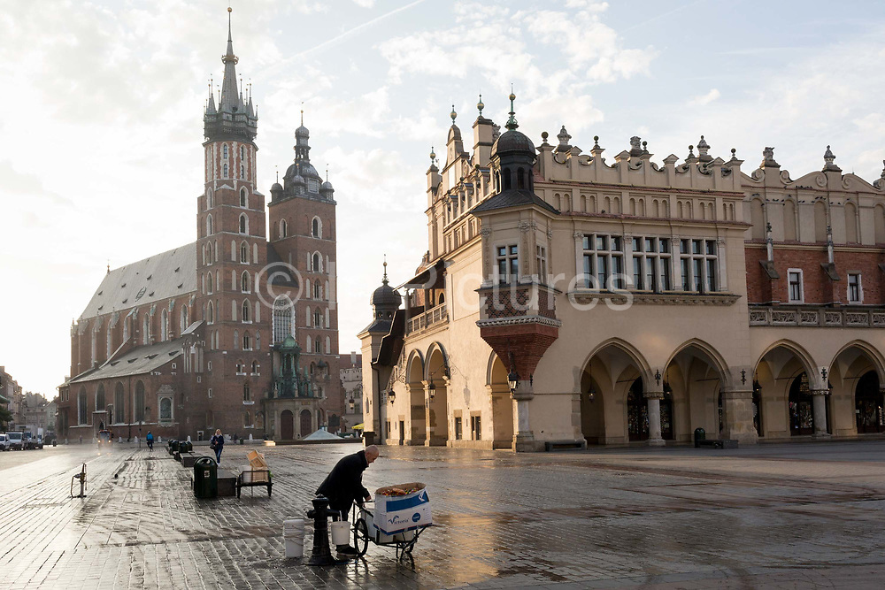 A flower seller fills buckets with fresh water beneath the towers of the Church of St Mary left and the Cloth Hall on Rynek Glowny market square, on 23rd September 2019, in Krakow, Malopolska, Poland.