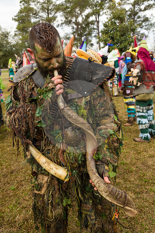 Costumed reveler blows a primitive horn to summon his group during the Faquetigue Courir de Mardi Gras chicken run on Fat Tuesday February 17, 2015 in Eunice, Louisiana. The traditional Cajun Mardi Gras involves costumed revelers competing to catch a live chicken as they move from house to house throughout the rural community.
