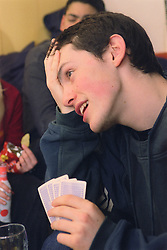 Teenage boy playing game of cards looking anxious,