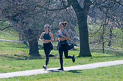 ©Licensed to London News Pictures 26/03/2020<br /> Greenwich, UK. Two young ladies enjoy a run in Greenwich Park, London this afternoon as people make the most of their permitted one a day exercise out of the house from Coronavirus Lockdown. The Prime Minister Boris Johnson has asked people to stay at home to help in the fight against Covid-19. Photo credit:Grant Falvey/LNP