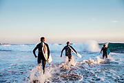 Surfers running into the surf and crashing waves at St ouen's Bay, Jwersey, CI at sunset
