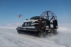 A giant Russian Mi8 helicopter (manufactured just a few hours away in Ulan-Ude) was on hand to make runs against the land based racers like this airboat on the mile long ice track. Baikal Mile Ice Speed Festival. Maksimiha, Siberia, Russia. Friday, February 28, 2020. Photography ©2020 Michael Lichter.