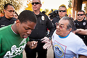 22 FEBRUARY 2011 - PHOENIX, AZ: Jarvis Johnson (CQ) GREEN TEE, a supporter of immigrants' rights and Arthur Olivas, (CQ) WHITE TEE a supporter of Sen Russell Pearce's anti-immigrant bills, debate immigration at the State Capitol in Phoenix Tuesday. Hundreds of people including supporters of immigrants' rights, supporters of border defense, motorcycle riders and members of the Tea Party, converged on the capitol to express their views on bills.     PHOTO BY JACK KURTZ