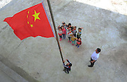 QIANNAN, CHINA - MAY 31: (CHINA OUT) <br /> <br /> Six-pupil School In Mountain Of Qiannan<br /> <br /> he only teacher Wu Guoxian and pupils hold a flag-rising ceremony at Gugang primary school in a mountain in Longli County on May 31, 2016 in Qiannan Buyei and Miao Autonomous Prefecture, Guizhou Province of China. Gugang primary school with only one teacher and six students was located in the mountain where the traffic was blocked in Qiannan. 50-year-old Wu Guoxian had been teaching in this school for 33 years and taught over 1,000 students. More and more people went out of the village to work in the cities leaving their children and the old in the mountain. Five under-school-age kids whose parents left for work also stayed at the school. <br /> ©Exclusivepix Media