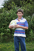 Model released casually dressed young boy holding a rugby ball