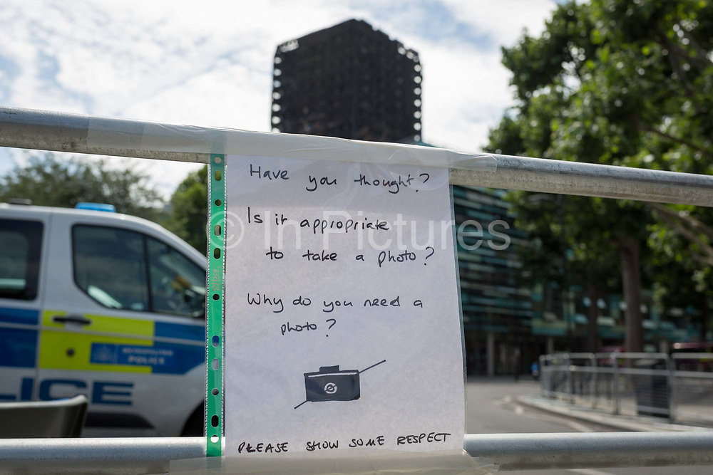 Twelve days after the devastating fire that killed an unspecified number of people in Grenfell Tower and while the tower block remains a crime scene, a notice posted by the local community urges visitors to the scene not to take pictures or selfies, on 26th June 2017, in the London borough of Kensington & Chelsea, England.