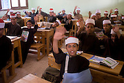 Schoolboys wave goodbye in their classroom at the Islamic Koom al-Bourit Institute for Boys in the village of Qum (Koom), on the West Bank of Luxor, Nile Valley, Egypt.