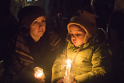 Westminster, London, December 2nd 2015.  As Parliament prepares to vote on air strikes on Islamic State terrorists in Syria, Stop The War and other groups opposed to British military involvement protest outside Parliament. PICTURED: A mother and her child hold a candlelit vigil. ///FOR LICENCING CONTACT: paul@pauldaveycreative.co.uk TEL:+44 (0) 7966 016 296 or +44 (0) 20 8969 6875. ©2015 Paul R Davey. All rights reserved.