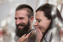 Close-up of couple listening on cell phone