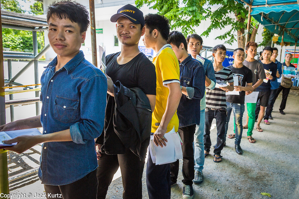 "17 JULY 2014 - BANGKOK, THAILAND: Undocumented Cambodian workers line up for their ID cards at the temporary ""one stop service center"" in the Bangkok Youth Center in central Bangkok. Thai immigration officials have opened several temporary ""one stop service centers"" in Bangkok to register undocumented immigrants and issue them temporary ID cards and work permits. The temporary centers will be open until August 14.    PHOTO BY JACK KURTZ"