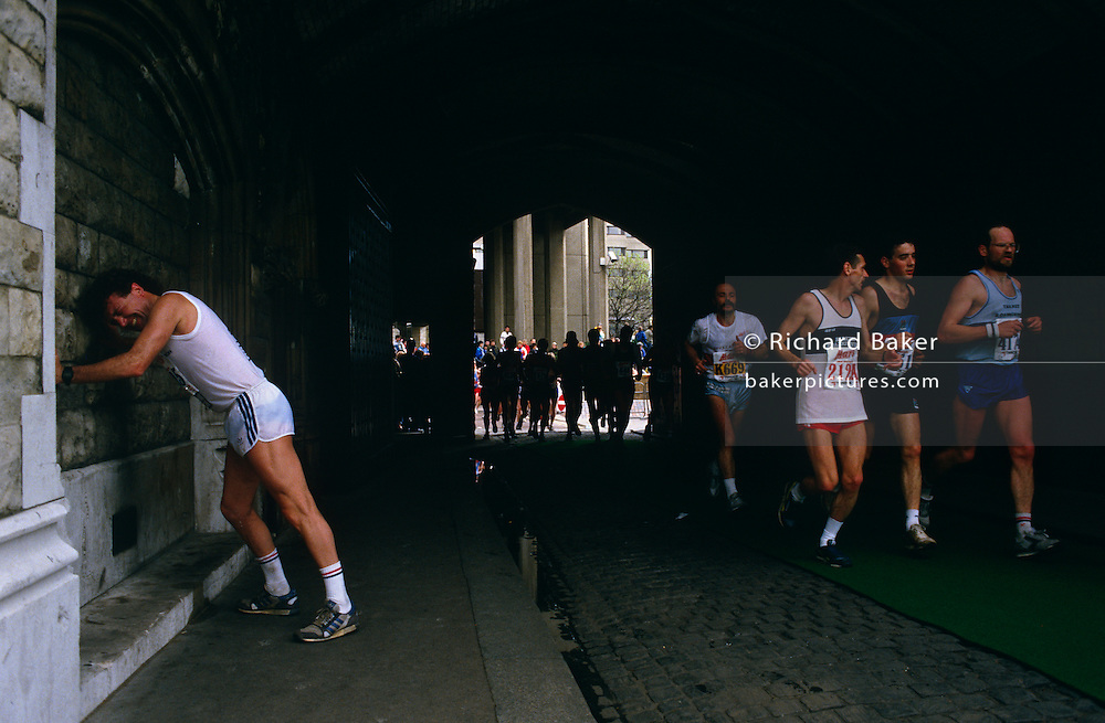 """A few miles from the finish line, this long-distance runner has stopped in agony to lean against the walls beneath Tower Bridge during th London Marathon, England. Pushing against the solid wall and stretching his cramped leg muscles, he grimaces in pain as other runners speed past on their way completing their personal race. Pushed to his limits, this man needs to continue a few more Kilometres to claim his medal and to claim victory. But he still has to overcome the pain of an overworked body. When glycogen runs low, the body must then burn stored fat for energy, which does not burn as readily. When this happens, the runner will experience dramatic fatigue. This is called """"hitting the wall""""."""