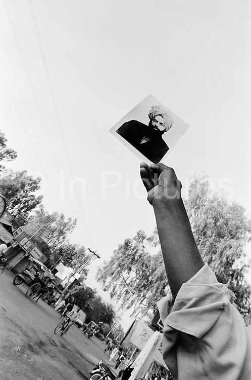A man holds a portrait of the prophet, Ahmed, Rabwah, Pakistan. Also known as Qadiani's The Ahmadiyyas are the followers of Hazrat Mirza Ghulam Ahmad Qadiani (1835-1908). According to his followers, he was the  founder of the Ahmadiyya Muslim Jama'at and The Promised Messiah and Imam Mahdi. The Ahmadiyya (Qadiani) movement in Islam is a religious organisation with more than 30 million members worldwide. Ahmadiyyas are now banned from calling themselves Muslim in Pakistan and suffer terrible discrimination under anti-blasphemy laws and are regularly murdered for their faith.