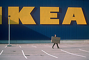 Seen from across an empty car park, a male customer carries away a flat packed purchase from Swedish home furnishing store Ikea. The giant company words appear as large yellow letters on the blue warehouse walls. The man of the family sees it as his role to buy the right unit and assemble the item at home using sequential instructions on the floor of a living room.  This store at Croydon in south London is a Mecca for lovers of flat-packed home furnishings.