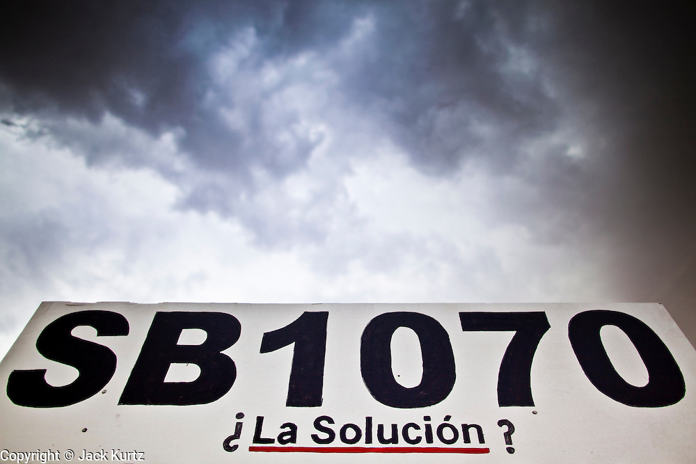 July 22 - PHOENIX, AZ: Storm clouds gather over a sign asking if SB 1070 is the solution to the illegal immigration crisis. About 50 people gathered on a street corner in a Hispanic neighborhood in Phoenix, AZ, Thursday night to pray the rosary. They are members of a Catholic community that opposes Arizona's tough new immigration law, SB 1070, which requires local police officers to check the immigration status of people they suspect of being in the US illegally and requires legal immigrants in Arizona to carry their immigration documents with them at all times. Photo by Jack Kurtz
