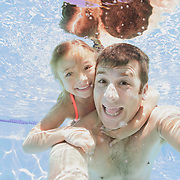 Father and daughter swimming in pool together. Model Release # ER20120624-00003/ER20120715-00002