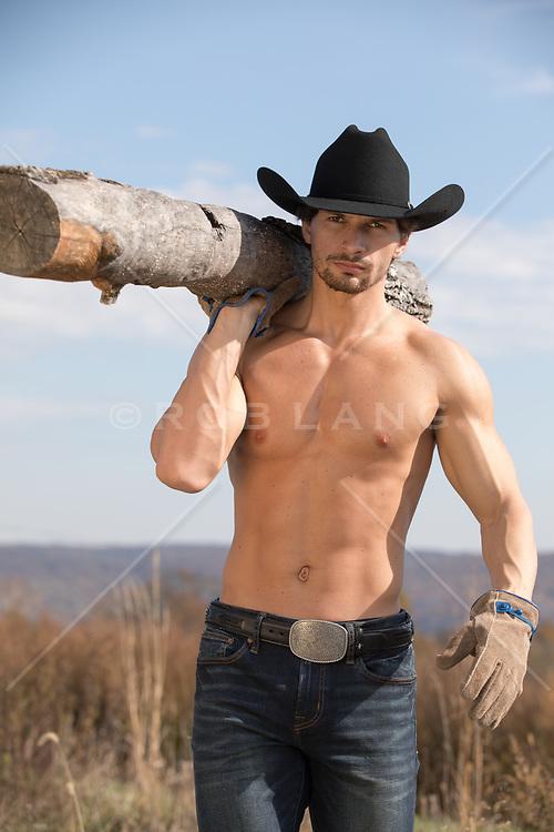 Shirtless cowboy hauling wood outdoors