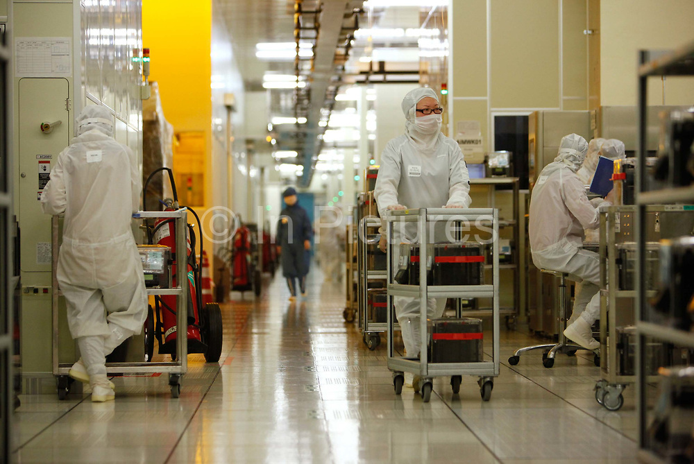 Employees operate in the wafer FAB of Semiconductor Manufacturing International Corp in Shanghai, China on 18 February, 2011.   The Taiwan based manufacturer is one of the largest chip foundries in the world.