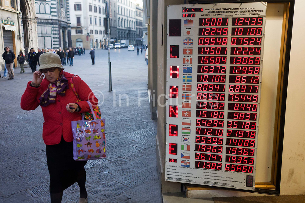 A bureau de change shop offers deals and best prices to tourists and Italian passers-by on a Florence street. With the countries' flags on the far left and across, are the buy and sell rates for the Euro. Lit with dot matrix numbers, the list of decimal figures can be seen from across the street. A local-looking lady walks past the store situated in a pedestrian street in the commercial centre of the city and we see the typical flag stones that line the pavements and roads.