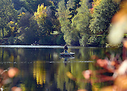 © Licensed to London News Pictures. 30/10/2012. Winkworth, UK A man in a fishing boat on Rowe's Flashe Lake. Autumn Colour at Winkworth Arboretum in Surrey today 30th October 2012. Photo credit : Stephen Simpson/LNP