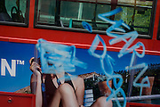 Advertising woman seen through blue graffiti on a bus in central London.