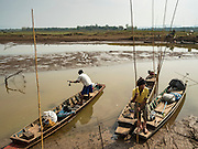 02 APRIL 2016 - NA SAK, LAMPANG, THAILAND: A fisherman lands his canoe near the original site of Sobjant village. The village of Sobjant in Na Sak district in Lampang province was submerged when the Mae Chang Reservoir was created in the 1980s. The village was relocated to higher ground a few kilometers from its original site. The drought gripping Thailand drained the reservoir and the foundations of the Buddhist temple in the original village became visible early in 2016. Thai families come down to the original village to pray in the ruins of the temple and look at what's left of the village.      PHOTO BY JACK KURTZ