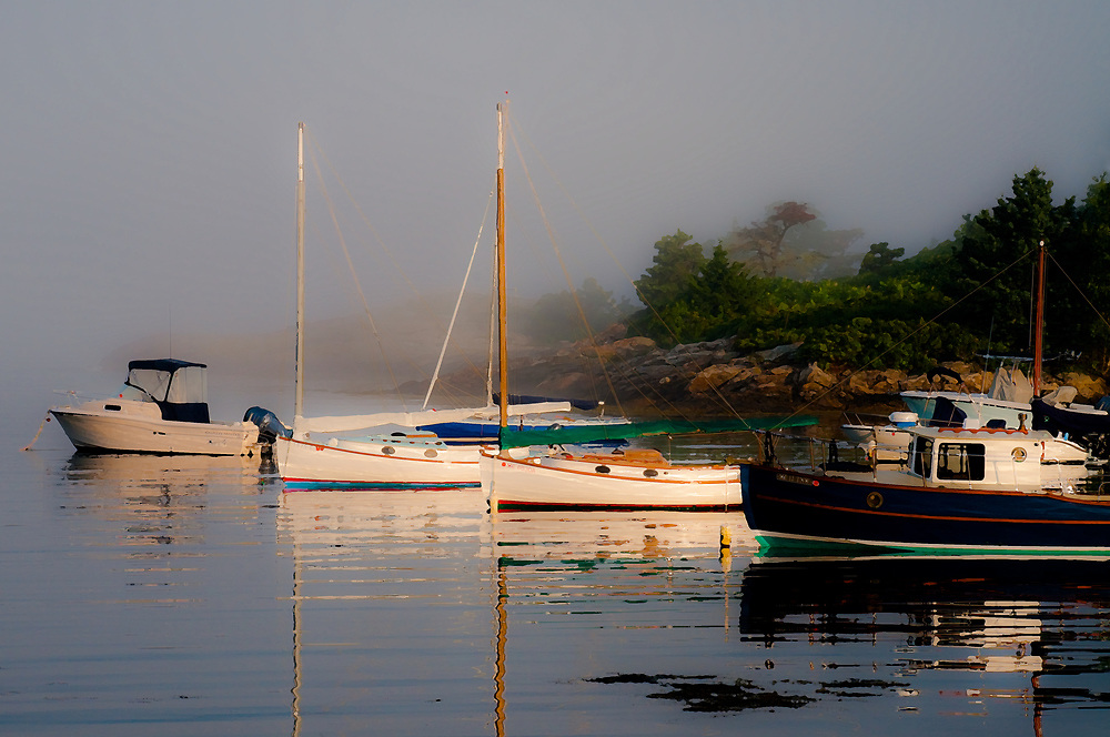 The first warmth of dawn paints boats and their reflections at Cozy Harbor on Southport Island while it burns off the morning mist.