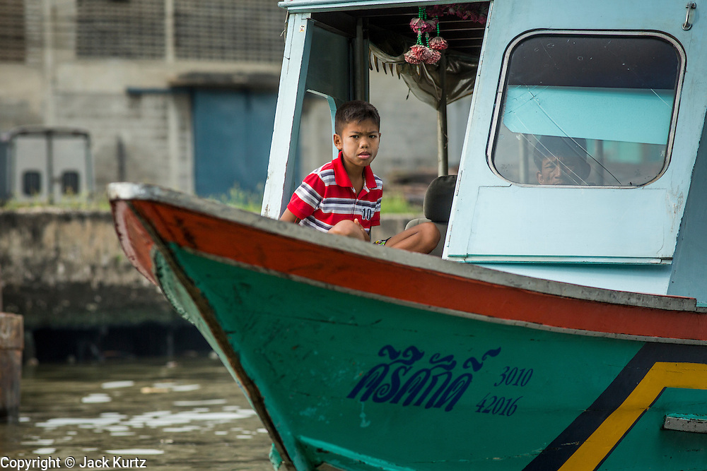"""17 NOVEMBER 2012 - BANGKOK, THAILAND:  A boy sits in the wheelhouse of his family boat on a canal in the Thonburi section of Bangkok. Bangkok used to be known as the """"Venice of the East"""" because of the number of waterways the criss crossed the city. Now most of the waterways have been filled in but boats and ships still play an important role in daily life in Bangkok. Thousands of people commute to work daily on the Chao Phraya Express Boats and fast boats that ply Khlong Saen Saeb or use boats to get around on the canals on the Thonburi side of the river. Boats are used to haul commodities through the city to deep water ports for export.    PHOTO BY JACK KURTZ"""