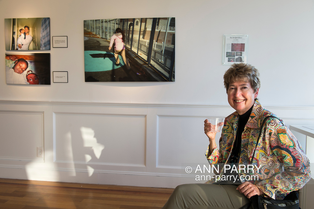 Huntington, New York, USA. August 1, 2015. HOLLY GORDON sits looking at photos at the Reception for Project Lives exhibition at fotofoto gallery, where she is a member. Over 200 residents throughout 15 New York Public Housing projects were given single use film cameras to photograph what's important to them in their world. All royalties from the sale of the book Project Lives will be donated to resident programs at NYC Housing Authority. The photos are: stepfather holding young girl Fuss by Janyia Ford, young brother sleeping by Aaliyah Colon, and girl running by Aaliyah Colon.