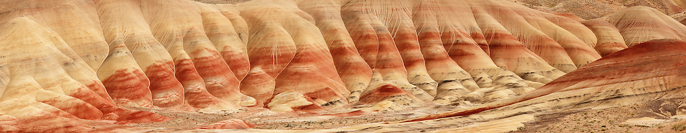 This panorama shows the colorful layers that give the Painted Hills in the John Day National Monument in Oregon their name. The layers represent different ash and pumice deposits from the Cascades and area volcanoes. The deposits were laid down approximately 33 million years ago. The red comes from rusty iron minerals; golden layers are rich with oxidized magnesium and iron, metamorphic claystone; the black comes from manganese.