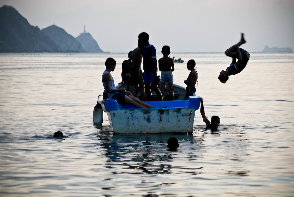 Children play on fishing boats after the day's catch has been dropped in the Colombian town Taganga.