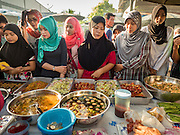 18 JUNE 2015 - PATTANI, PATTANI, THAILAND:    Muslim women shop in the Pattani Ramadan Bazaar, a sprawling street food market that is open during Ramadan. People come to the street food market late in the day to buy meals for the evening Iftar meal, which breaks the day long fast. Ramadan is the ninth month of the Islamic calendar, and is observed by Muslims worldwide as a month of fasting to commemorate the first revelation of the Quran to Muhammad according to Islamic belief. This annual observance is regarded as one of the Five Pillars of Islam. Islam is the second largest religion in Thailand. Pattani, along with Narathiwat and Yala provinces, all on the Malaysian border, have a Muslim majority.       PHOTO BY JACK KURTZ