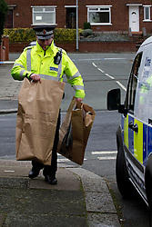 © licensed to London News Pictures. Salford, UK  27/02/2012. A police officer carries children's toys in evidence bags from a taped off area at the scene where two men are reported as having been shot. Police close off several streets in Claremont, Salford after two men were shot and blood was found in the street. Photo credit should read Joel Goodman/LNP
