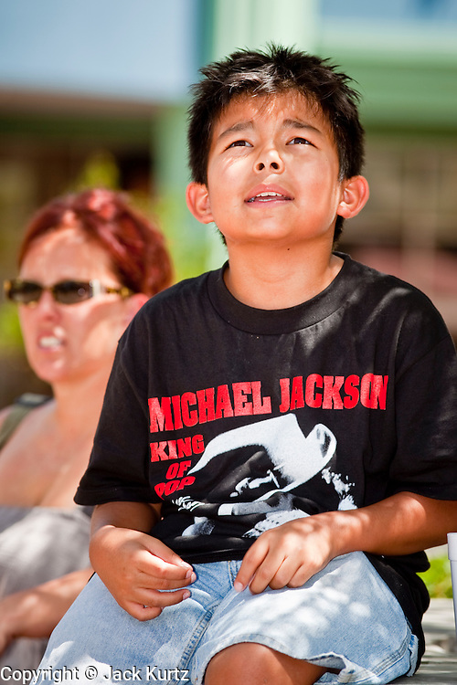 Jul 7, 2009 -- GLENDALE, AZ: TYE ROMERO, 11, from Avondale, AZ, watches the memorial for Michael Jackson in Glendale, AZ, Tuesday. About 35 people came to Westgate Center, a shopping and dining complex in Glendale, a suburb of Phoenix, AZ, to watch the memorial service for Michael Jackson. The service was simulcast live from the Staples Center in Los Angeles on jumbotrons around the complex. Photo by Jack Kurtz