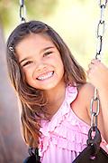 Cute Hispanic Girl Swinging At The Park