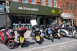 © Licensed to London News Pictures. 13/05/2020. London, UK. Delivery drivers wait outside the Harrow McDonald's alongside a row of motorbikes. McDonald's has reopened 15 stores in the south east for delivery only service through Uber Eats. Photo credit: Peter Manning/LNP